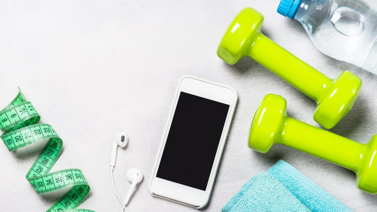 workout equipment including weights, water, headphones, iPhone, and measuring tape