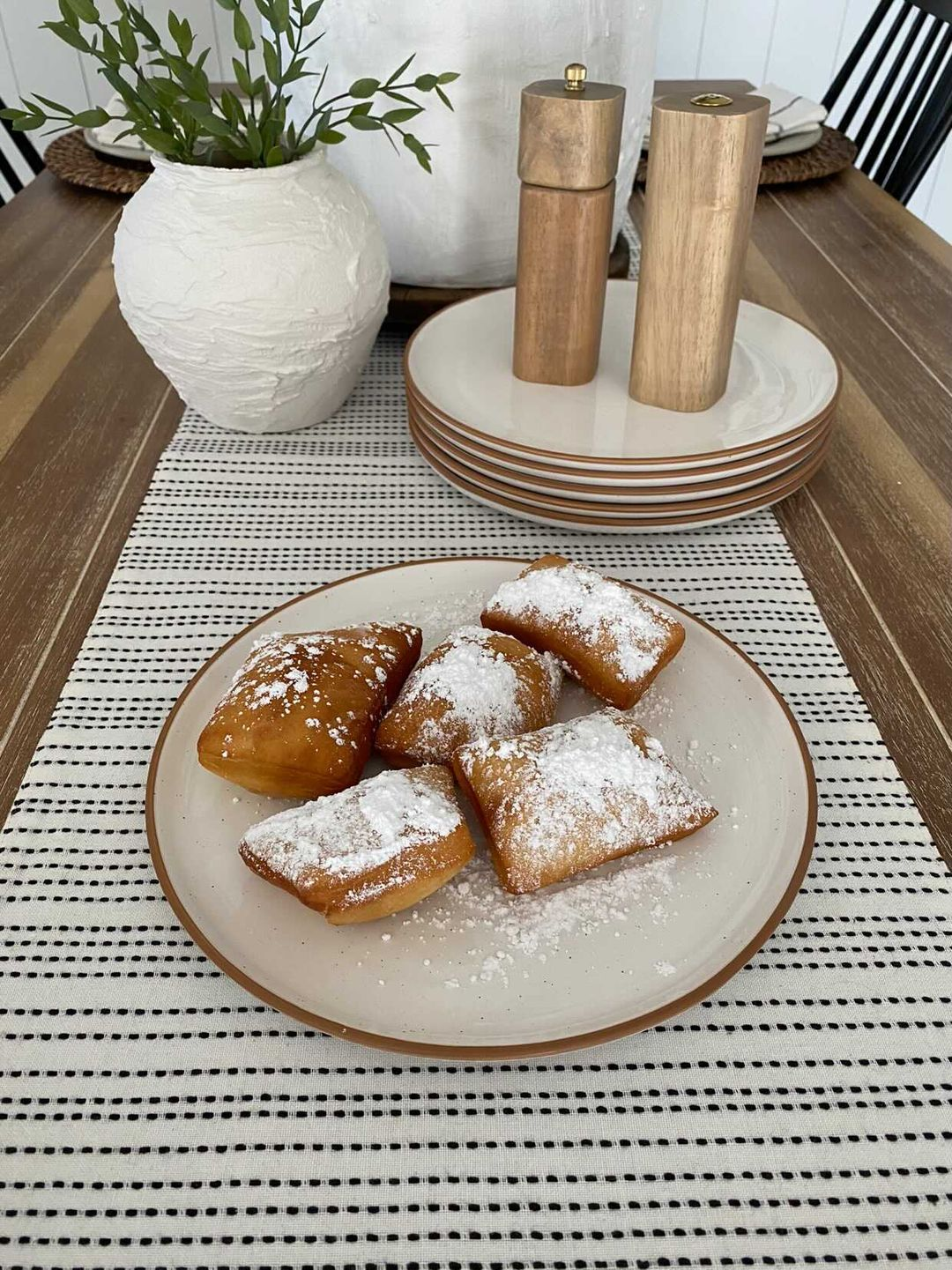 beignets on a Mora Ceramics plate dusted with powdered sugar
