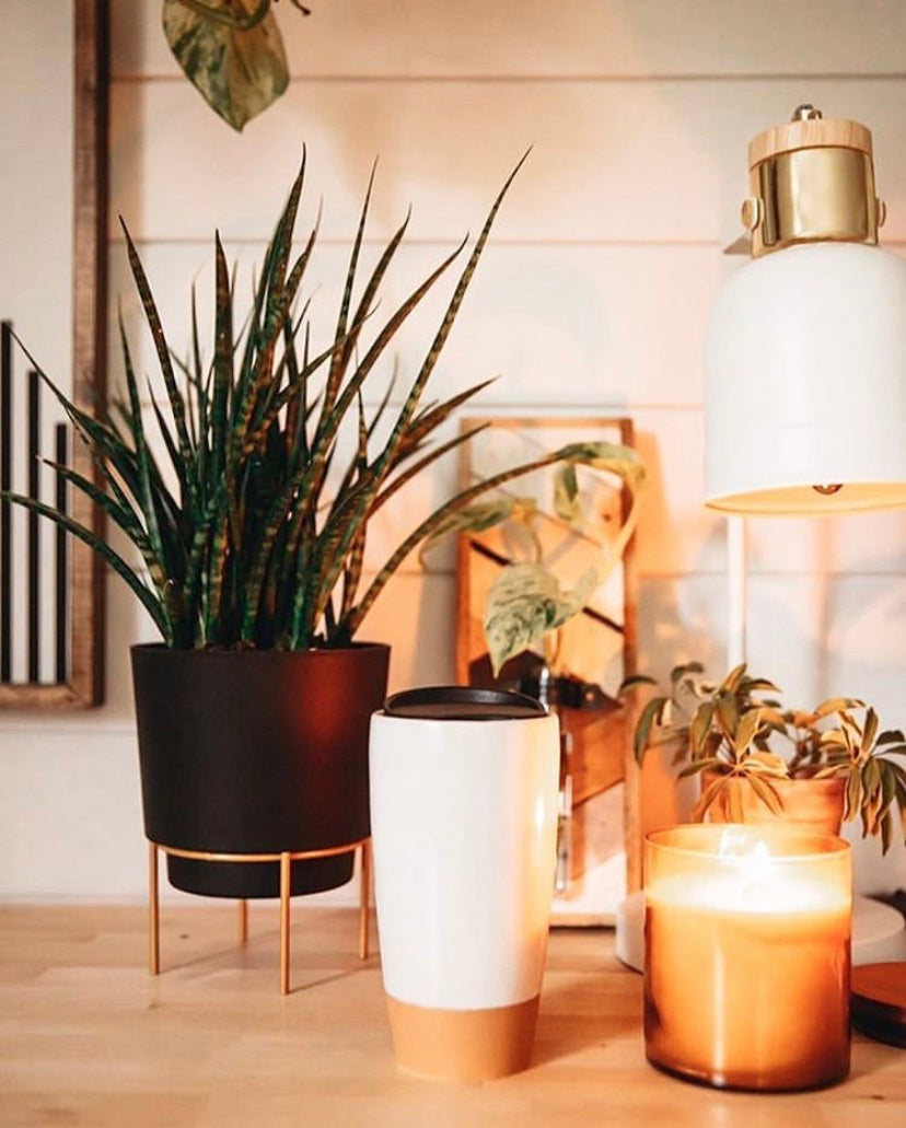 mora ceramic travel mug on a desk with a candle and plant