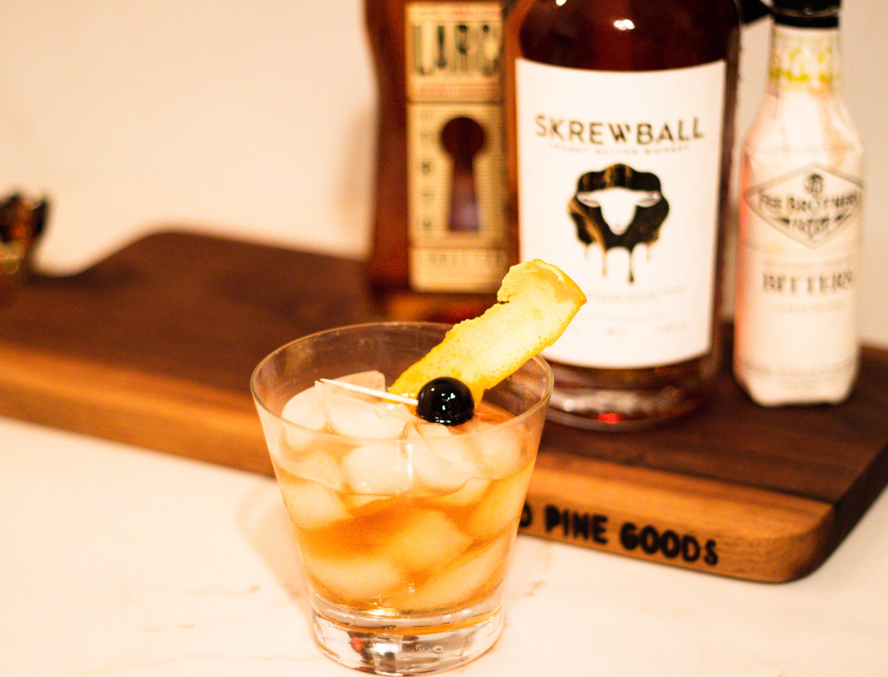 Peanut Butter Old Fashioned with skrewball whiskey, an orange peel, and a cherry
