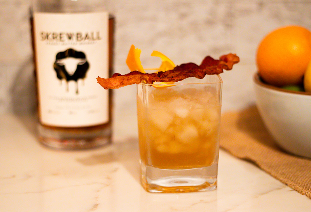 Peanut Butter Maple Bacon Old Fashioned with skrewball whiskey and an orange peel