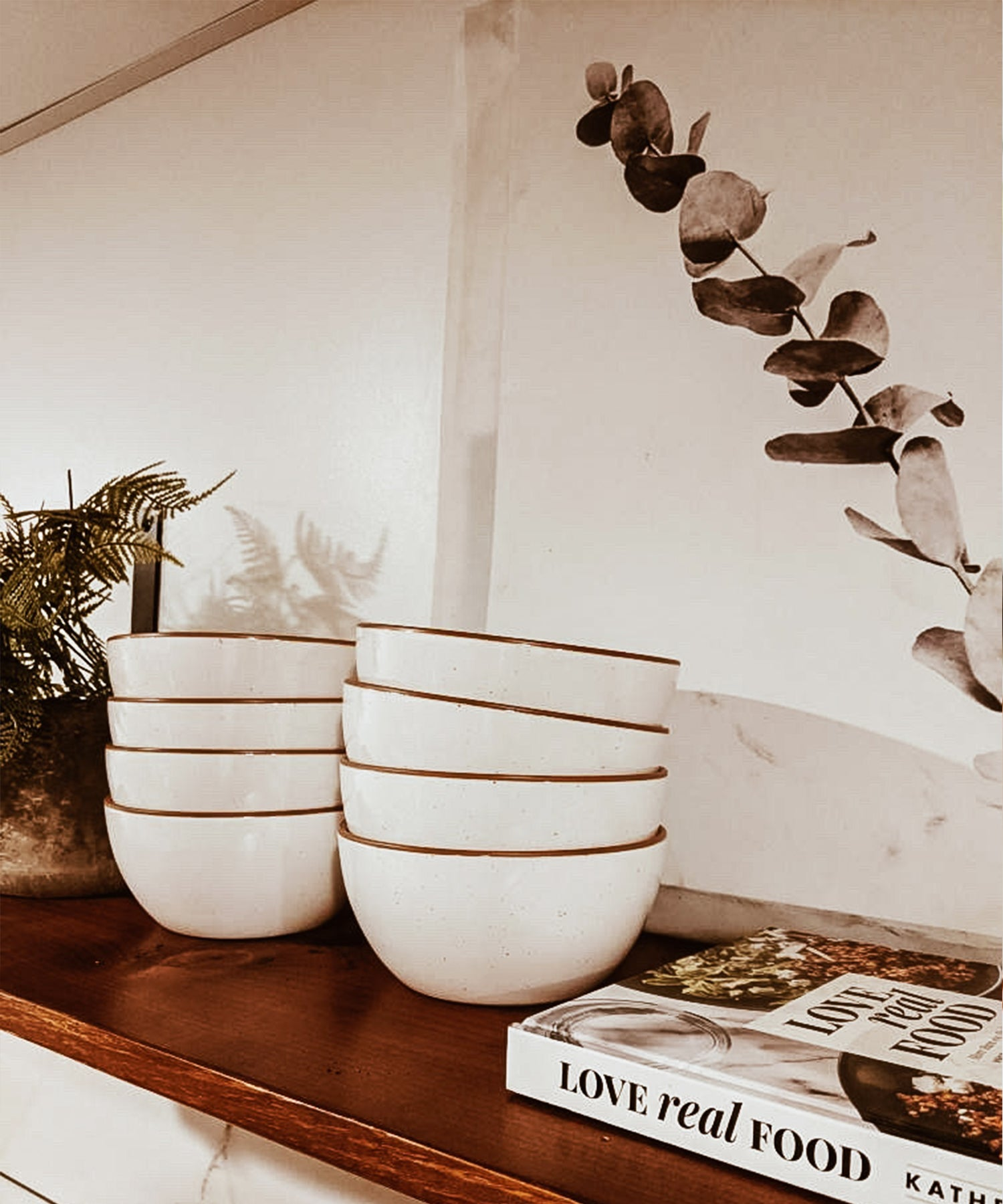 set of 8 stacked white speckled cereal bowls with brown rims on a wooden shelf with a eucalyptus plant