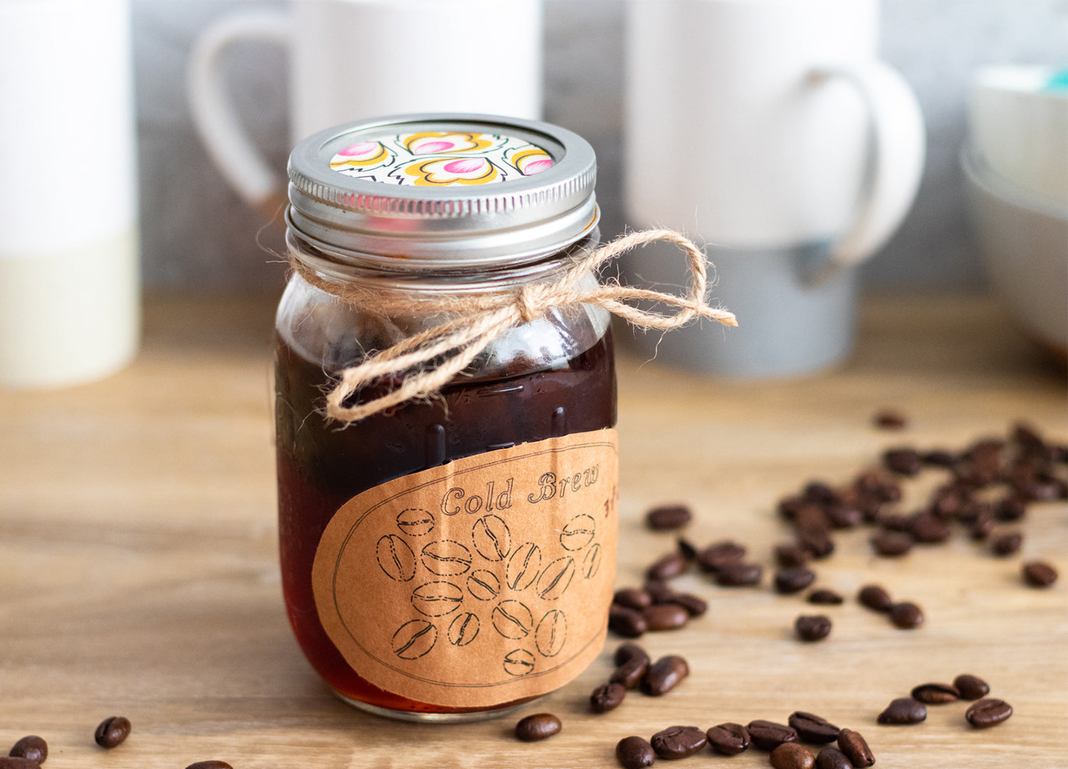 Fully extracted cold brew coffee in a mason jar with a Cricut made cold brew label, decorative twine, and a pink and yellow decorative sticker