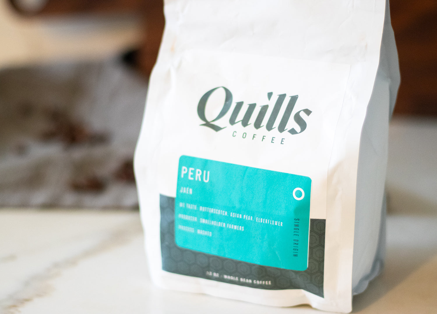 Quills Peru coffee bean bag resting on a counter ready to be ground