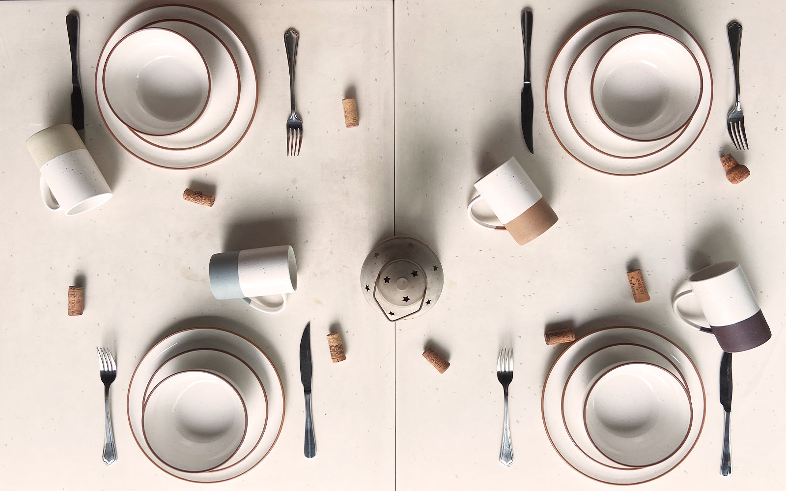 aerial view of a white table setting with rimmed dinner plates, salad plates, cereal bowls, and coffee mugs