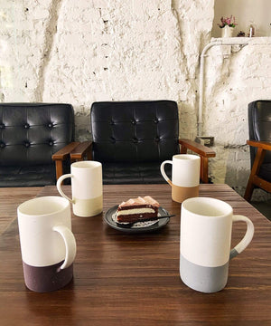Mora Ceramics set of 4 coffee mugs on a table at a modern cafe with cake and leather chairs