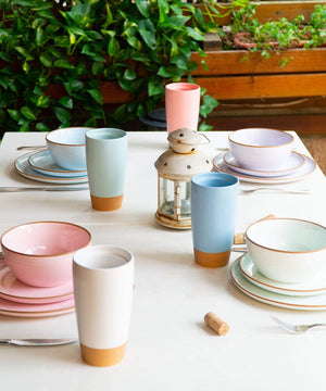 whimsical table setting with colorful ceramic plates, bowls and travel mugs Mora Ceramics