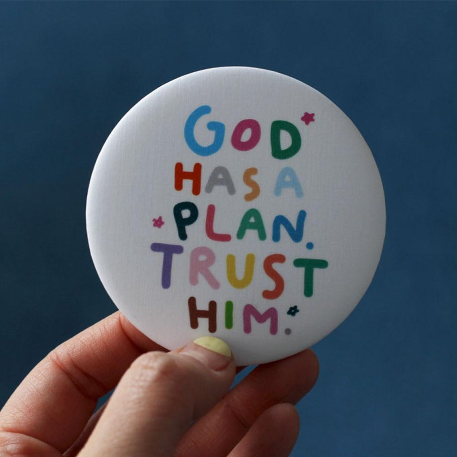 white circular pocket mirror with the pastel encouragement words 'God has a plan. Trust him.'