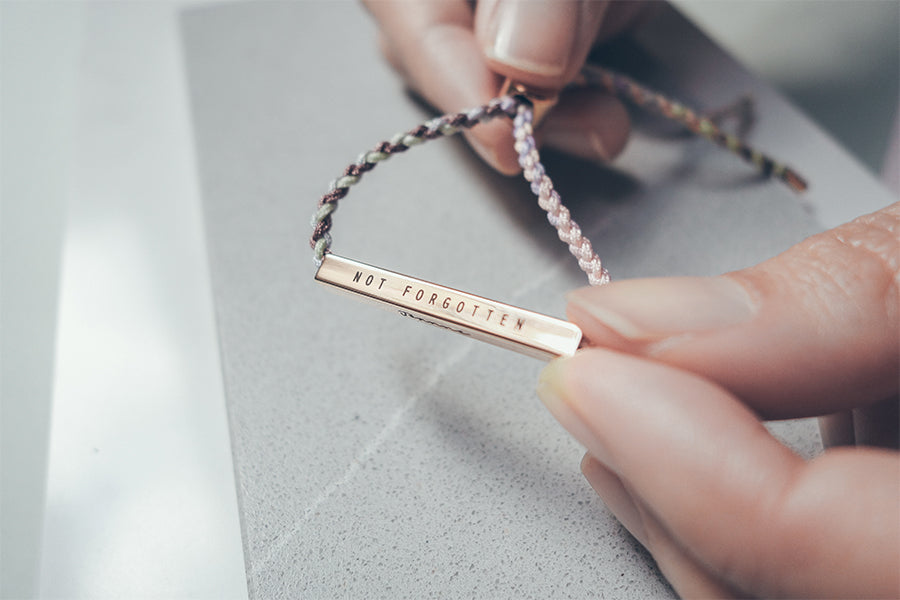the words 'not forgotten' is engraved on the rose gold stainless steel bar attached to paddle pop macrame rope.