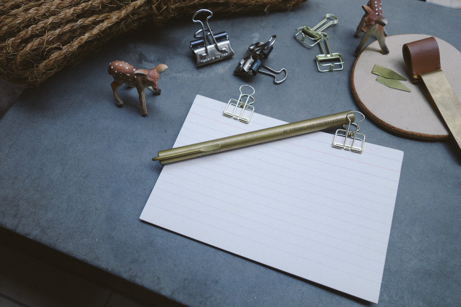 brass pen on notepad with brass paperclips and other brass accessories nearby. Aesthetic stationery photograph.