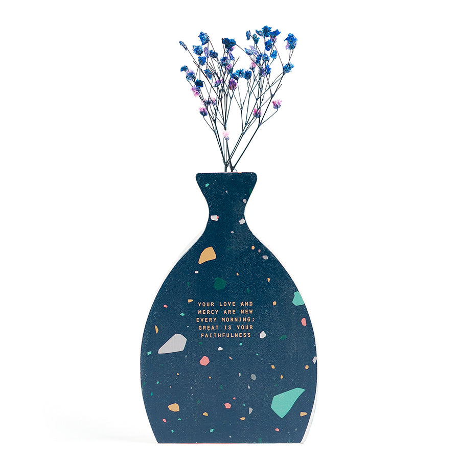 Wooden house in the shape of a blue vase. With flowers details and blue letter typography of 'Your love and mercy are new every morning; great is your faithfulness'. Decorated with dried blue and pink baby's breath.