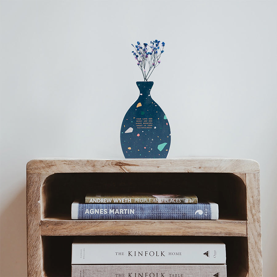 Wooden vase in the shape of a brush swatch vase decorated with dried blue and pink baby's breath. Placed on top of a bookshelf which is stocked with three books.