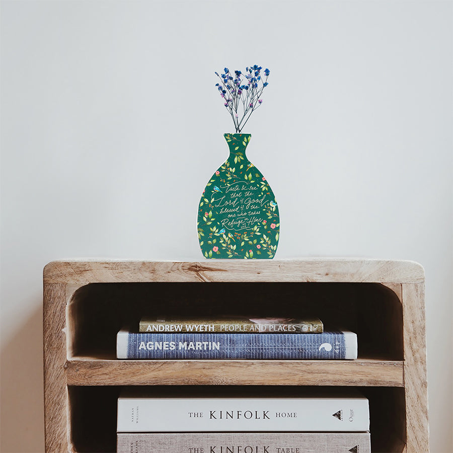 Wooden vase in the shape of a green vase decorated with dried blue and pink baby's breath. Placed on top of a bookshelf which is stocked with three books.