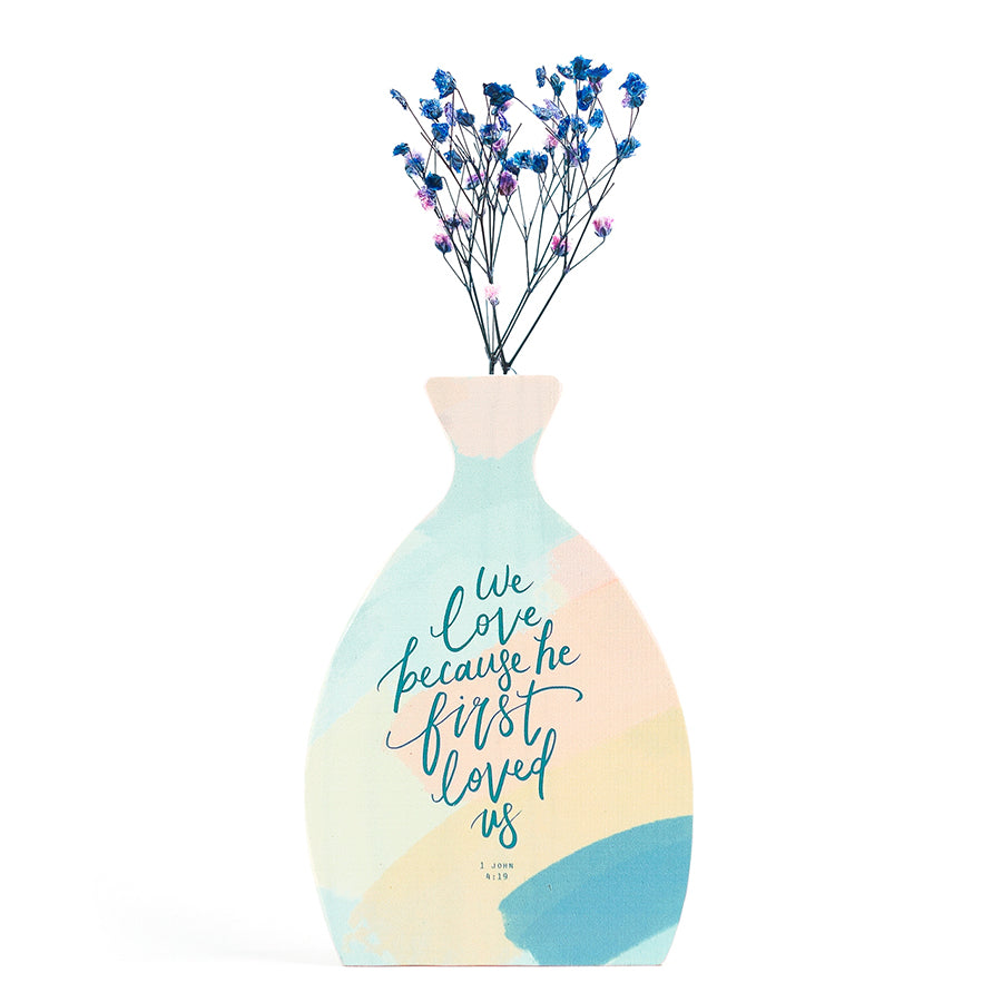 Wooden vase in the shape of a brush swatch vase. With flowers details and blue letter typography of 'We love because we first loved us'. Decorated with dried blue and pink baby's breath.