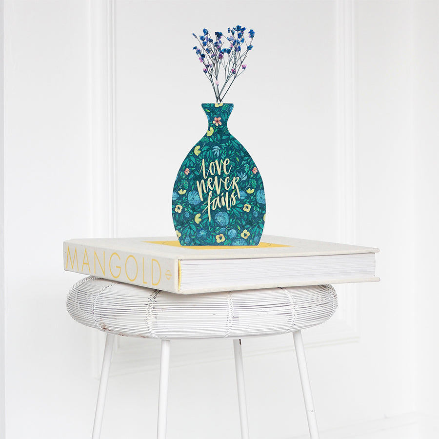 Wooden vase in the shape of a blue vase decorated with dried blue and pink baby's breath. Placed on a book on a white rattan stool.