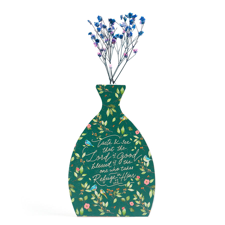 Wooden vase in the shape of a green vase. With flowers details and white letter typography of 'Taste and see that the Lord is good'. Decorated with dried blue and pink baby's breath.