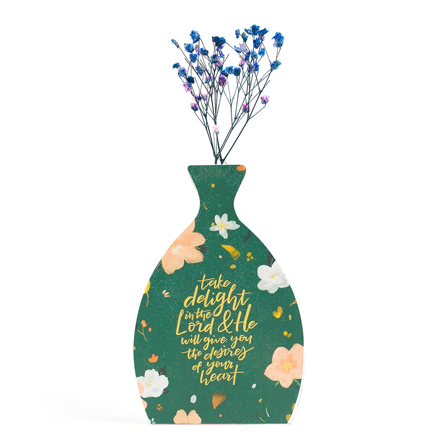 Wooden vase in the shape of a green vase. With flowers details and white letter typography of 'Take delight in the Lord'. Decorated with dried blue and pink baby's breath.