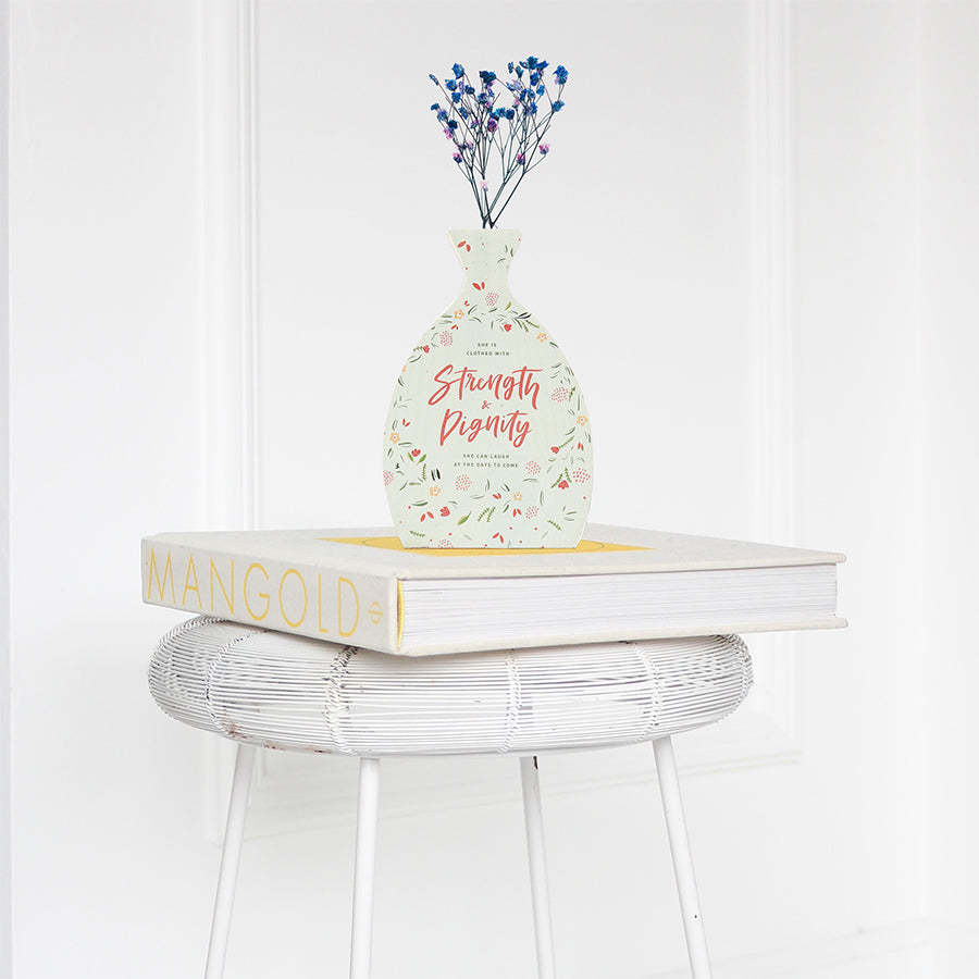 Wooden vase in the shape of a vial decorated with dried blue and pink baby's breath. Placed on a book on a white rattan stool.