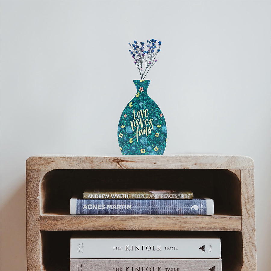 Wooden vase in the shape of a vial decorated with dried blue and pink baby's breath. Placed on top of a bookshelf which is stocked with three books.
