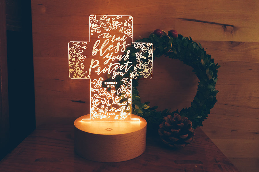 Night light in the shape of a cross placed in front of a wreath and a pine cone.