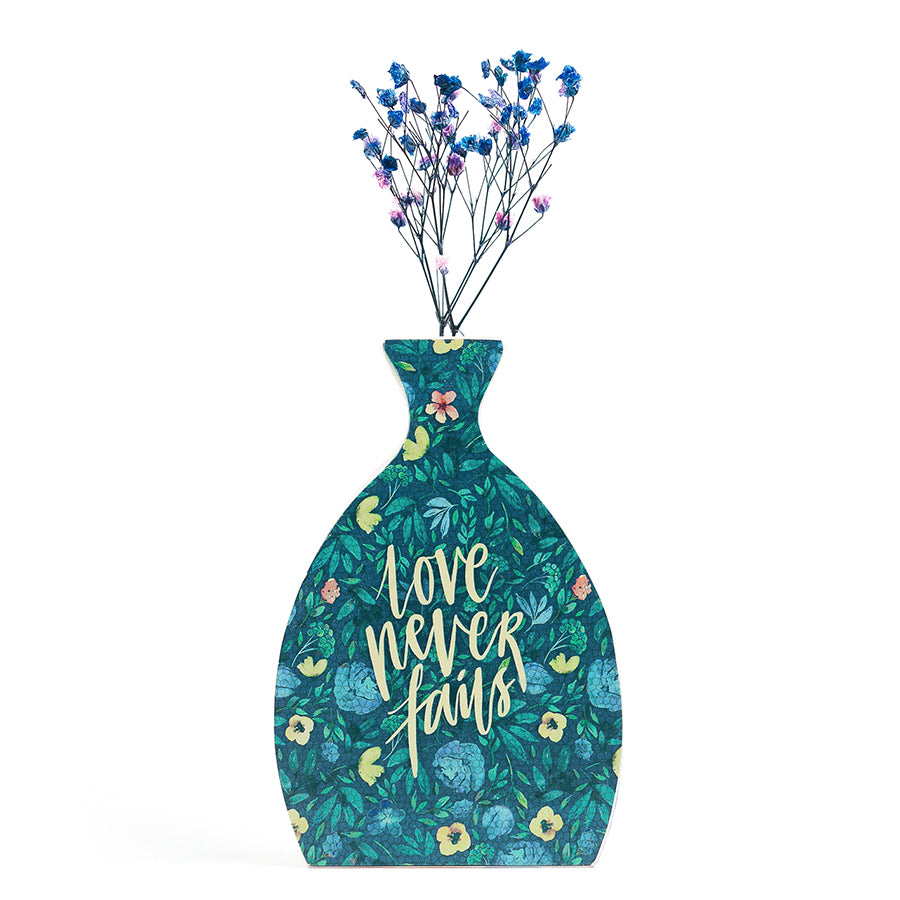 Wooden vase in the shape of a vial. With floral details and white letter typography of 'Love never fails'. Decorated with dried blue and pink baby's breath.