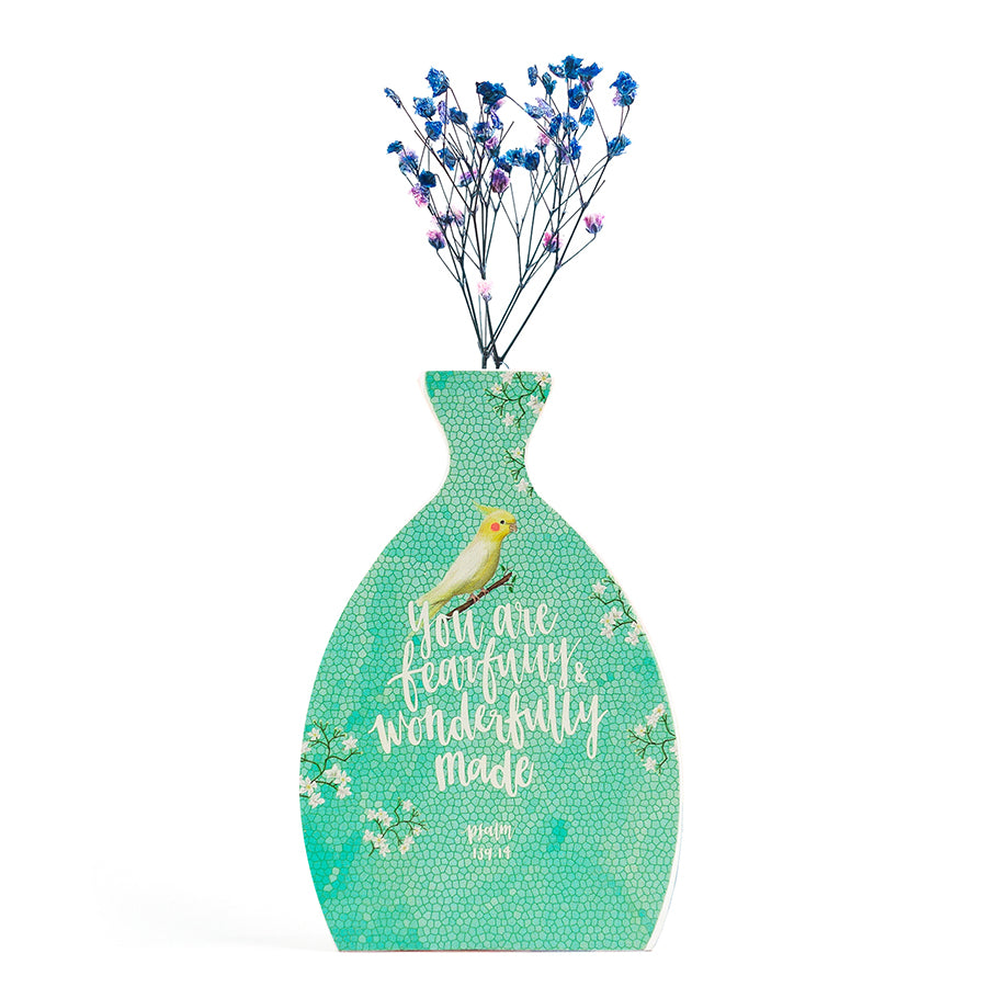 Wooden vase in the shape of a vase. With leaves details and white letter typography of bible verse 'you are fearfully and wonderfully made'. Decorated with dried blue and pink baby's breath.