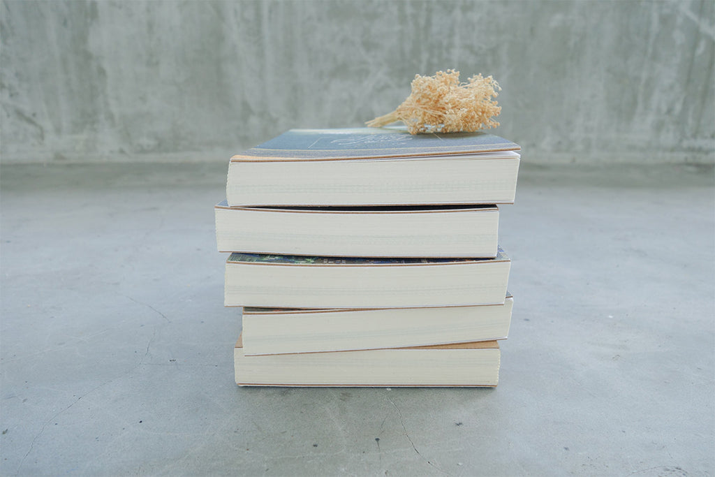 5 books stacked together with gold dried flowers as decoration