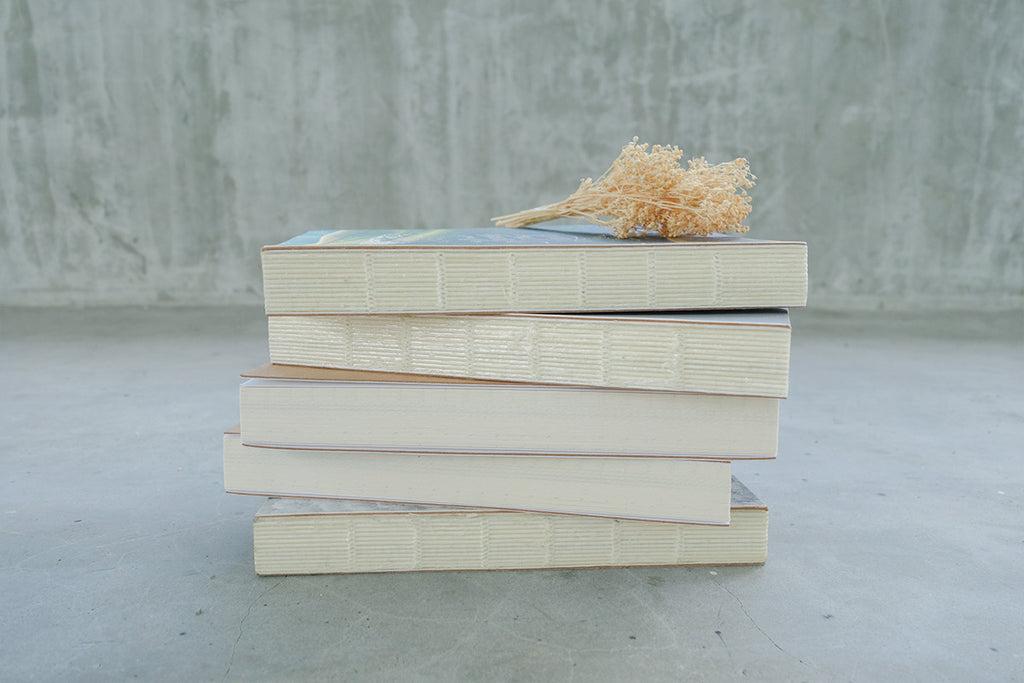 Side view of 5 notebooks stacked together with yellow dried flowers on top as decoration.