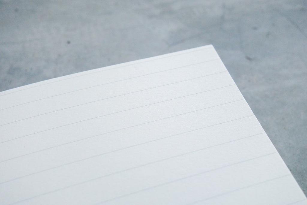 horizontally lined pages of the notebook