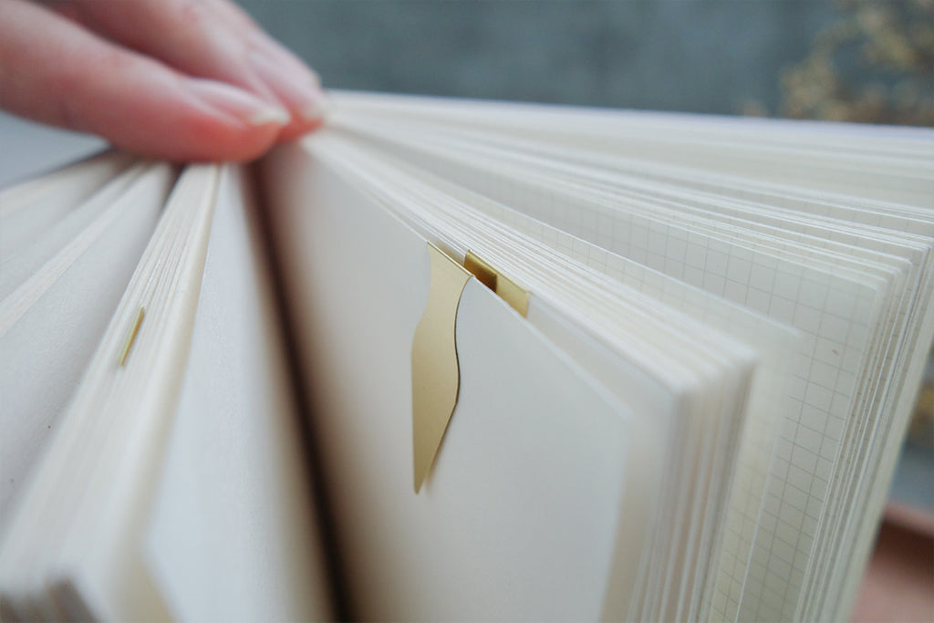 Close up of the different pages of the notebook, with metal bookmarks decoration.