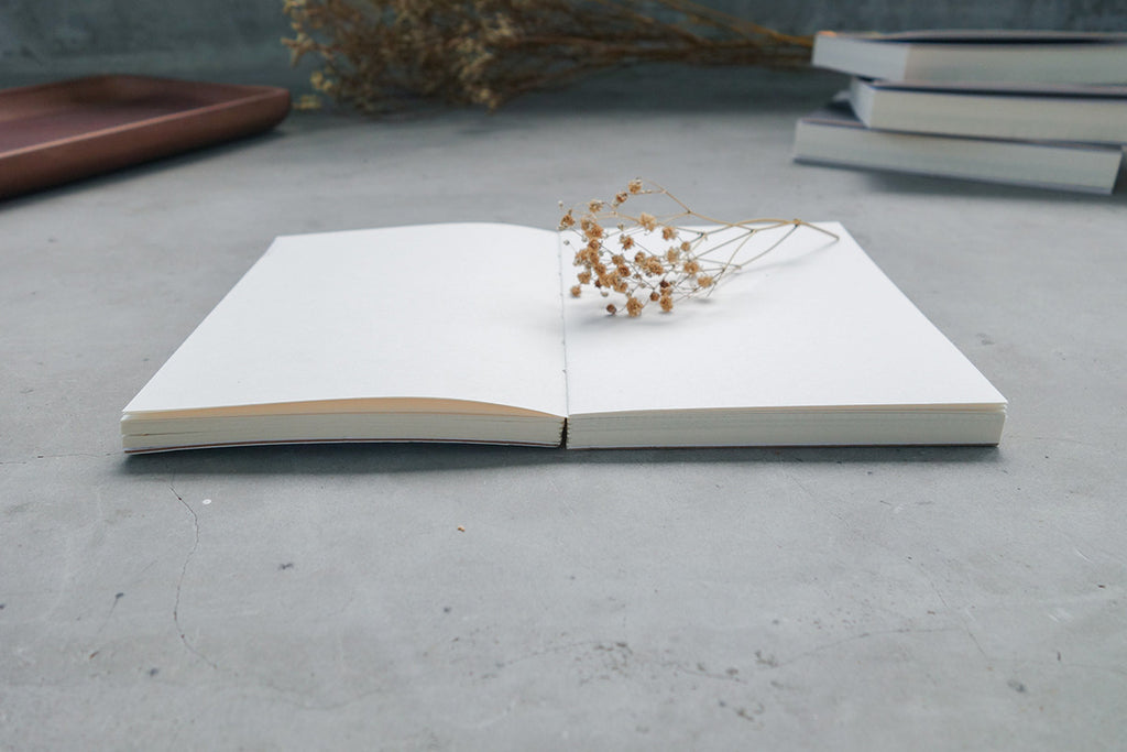 Notebook lays flat when parted in the centre. Decorated with dried baby's breath.