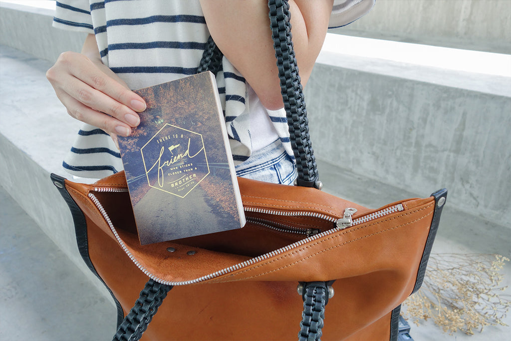 The notebook is being put into leather handbag