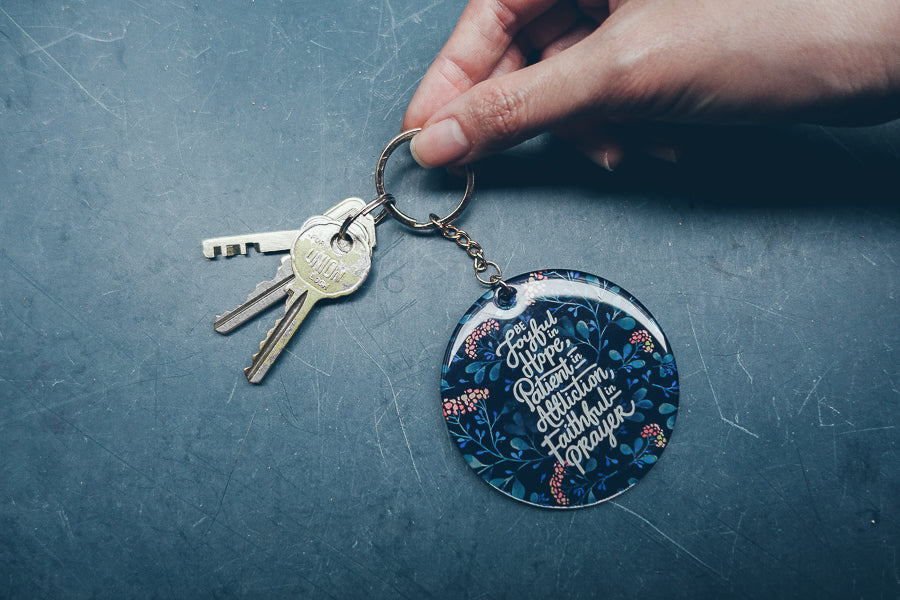 Dark blue circular keychain used for organising keys. It features inspirational bible verses