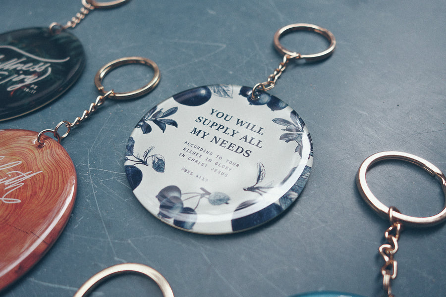 White circular acrylic keychain carrying inspirational quotes from the bible, designed by The Commandment Co
