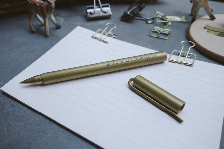 Brass pen with cap off on top of notepad.