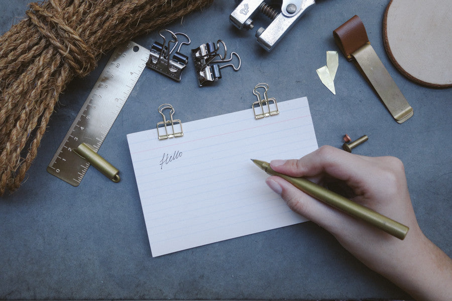 "The brass pen being used to write the word ""Hello"" on a notepad."