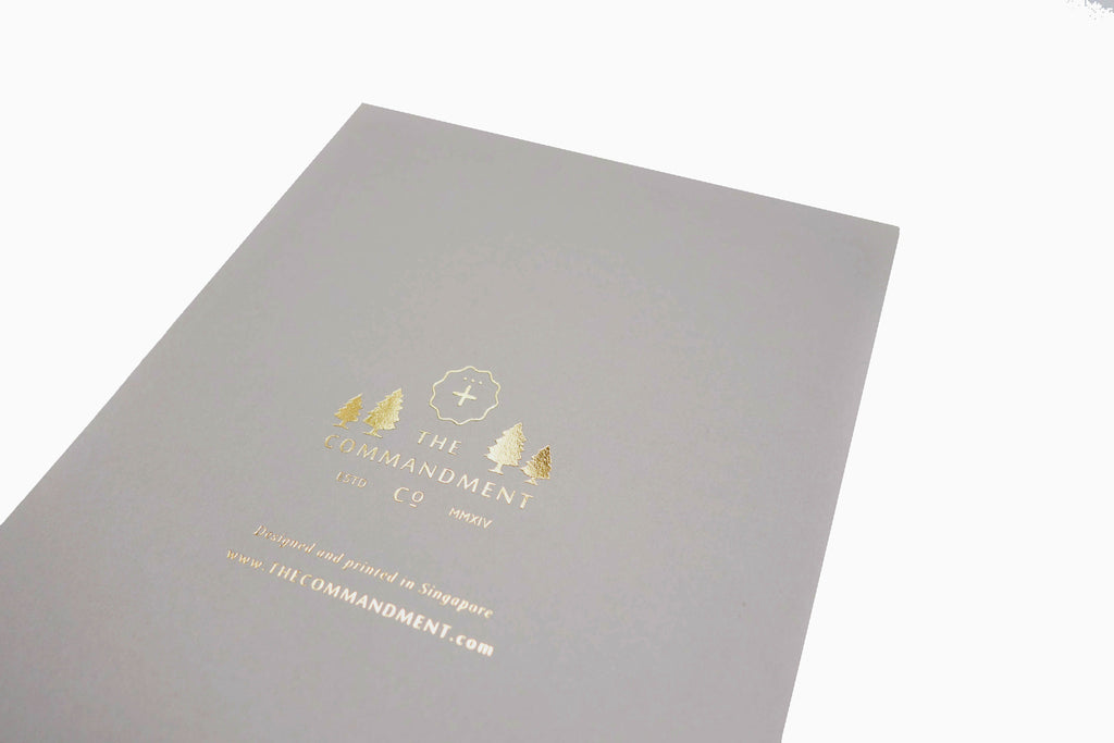 Close up of The Commandment Co logo in gold at the back of the gray card