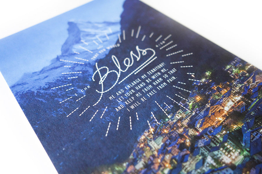 Close up of card verse design 1 Chronicles 4:10 on a background of a well lit town with a mountain surrounding it.