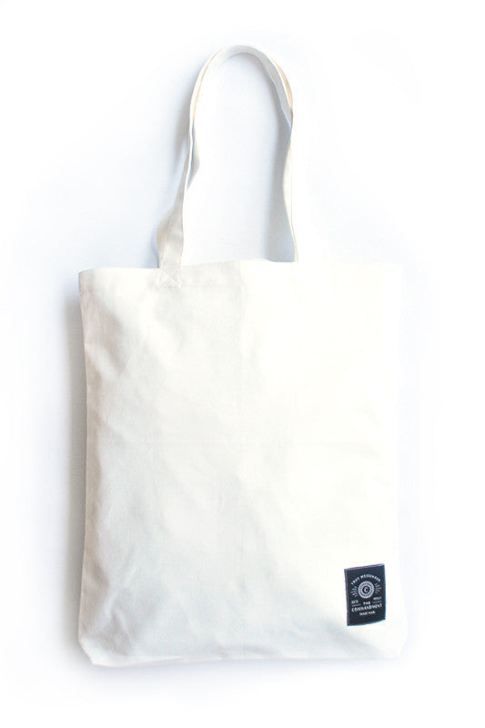 Back view of the white tote bag features the small Commandment co logo in the bottom right