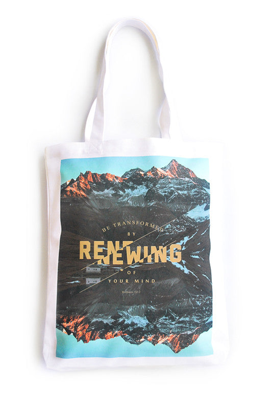 Tote bag made of 100% organic cotton from India. Features a design from Romans 12:2 Be transformed by the renewing of your mind, gold letters on top of mountaintops background.