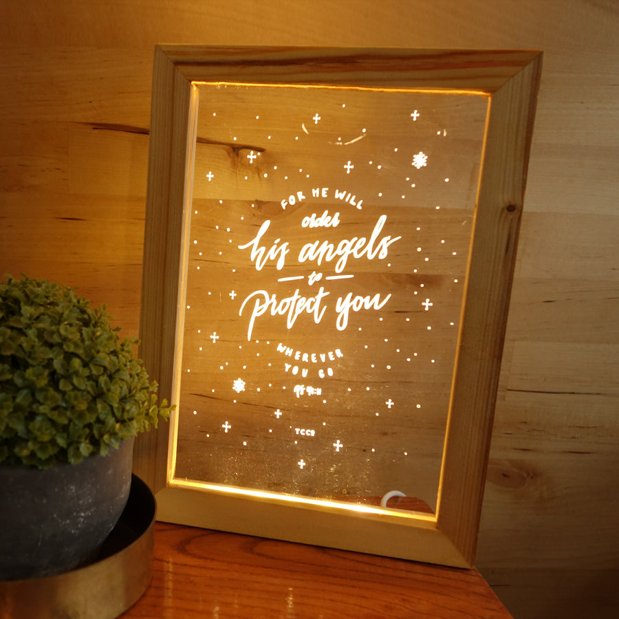 "Night light with wooden frame, acrylic insert, LED energy saving warm white light. 17cmx23cm measurements. Snowflake details with ""for he will order his Angels to protect you wherever you go"" typography."