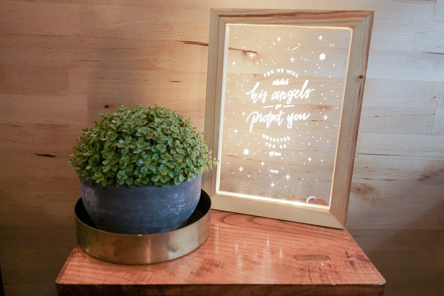 "Night light with wooden frame, acrylic insert, LED energy saving warm white light. 17cmx23cm measurements. Snowflake details with ""for he will order his Angels to protect you wherever you go"" typography. Placed next to a potted plant"