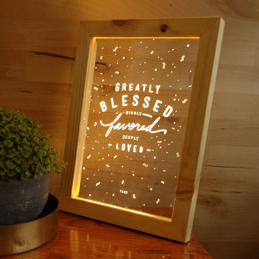 "Night light with wooden frame, acrylic insert, LED energy saving warm white light. 17cmx23cm measurements. Snowflake details with ""Greatly blessed highly favoured deeply favoured"" typography."