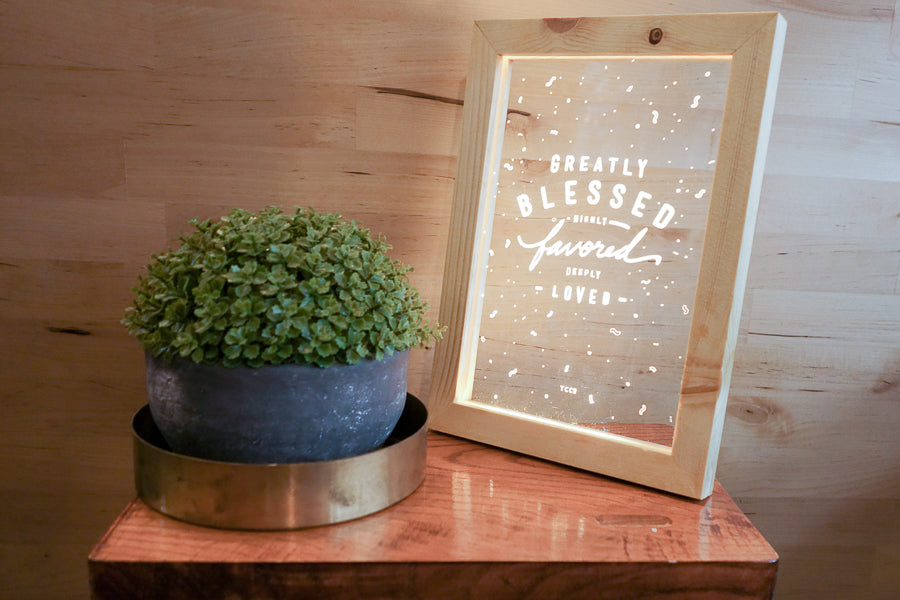 "Night light with wooden frame, acrylic insert, LED energy saving warm white light. 17cmx23cm measurements. leaves details with "" Greatly blessed highly favoured deeply favoured "" typography. Placed in front of other night lights on a wooden shelf."