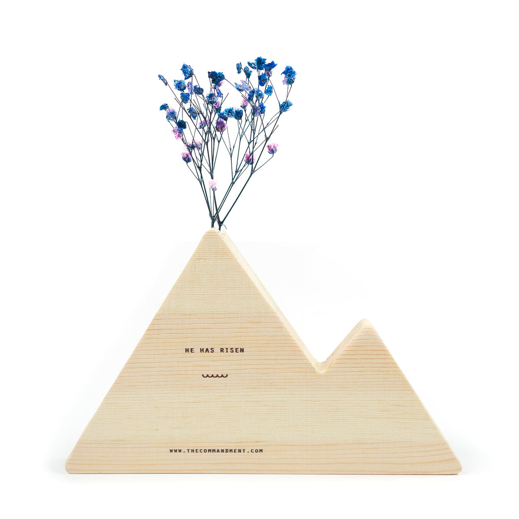 The mountain wooden vase has the word 'He has risen' at the back.