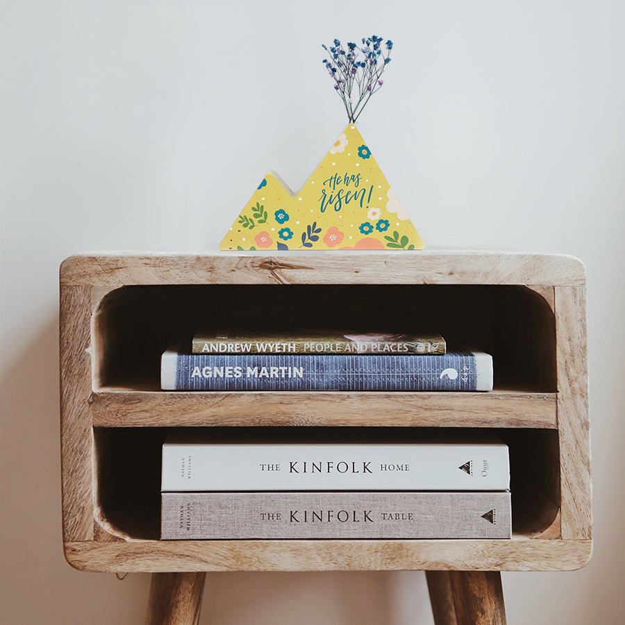 Wooden vase in the shape of a yellow mountain decorated with dried blue and pink baby's breath. Placed on top of a bookshelf which is stocked with three books.