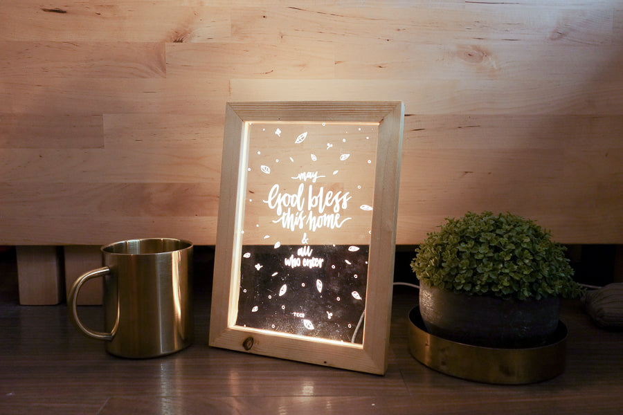 "Night light with wooden frame, acrylic insert, LED energy saving warm white light. 17cmx23cm measurements. leaves details with "" May God bless this home and all who enter "" typography. Placed in front of other night lights on a wooden shelf."