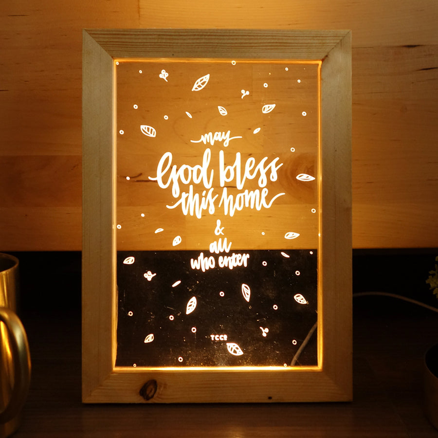 "Night light with wooden frame, acrylic insert, LED energy saving warm white light. 17cmx23cm measurements. Snowflake details with ""May God bless this home and all who enter"" typography."