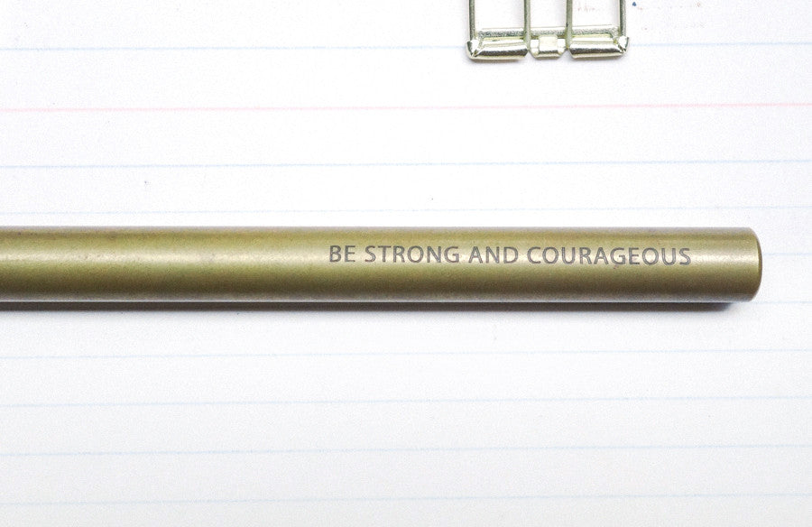 "Close up of engraving ""Be strong and courageous"" design on the barrell of a brass pen."