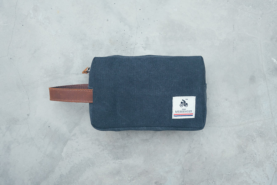 Navy blue toiletry bag with leather handle.